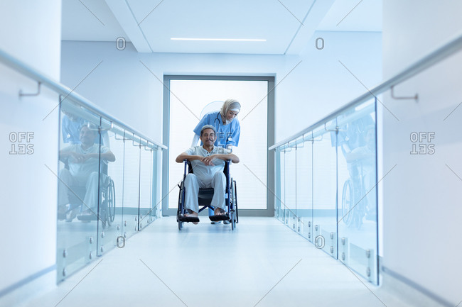 Front view of mixed-race female doctor in hijab pushing senior mixed-race male patient in wheelchair at corridor in hospital.