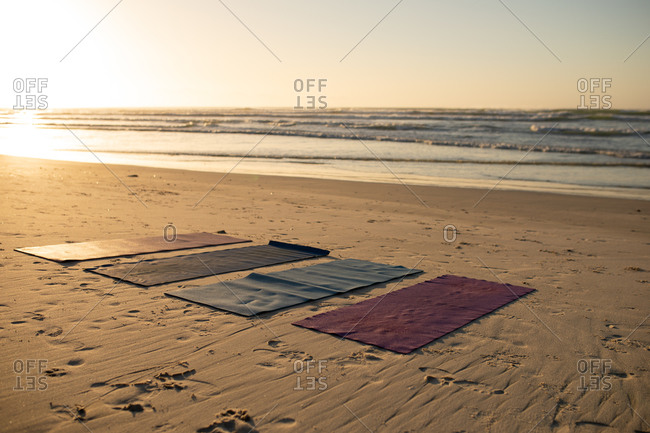 General view of four yoga mats on the beach by the sea on a sunny day with a stunning view of calm sea.