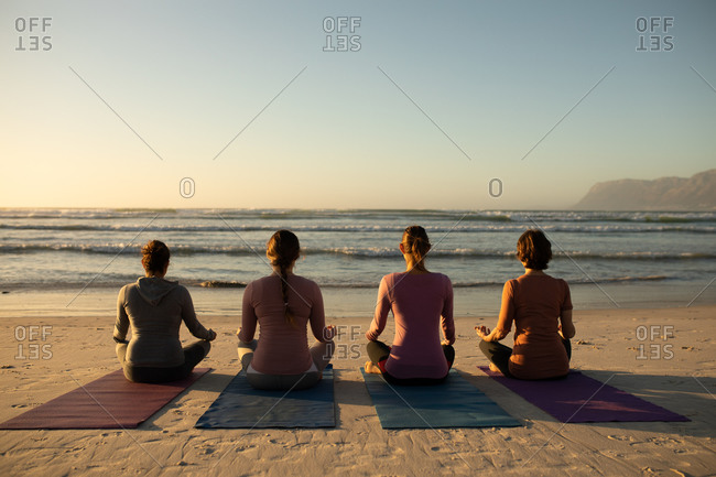 Rear view of a multi-ethnic group of female friends enjoying exercising on a beach on a sunny day, practicing yoga sitting and meditating, facing the sea.