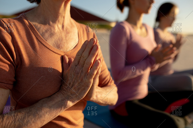 Side view mid section of a multi-ethnic group of female friends enjoying relaxing on a beach on a sunny day, practicing yoga sitting and meditating, with hands in prayer.