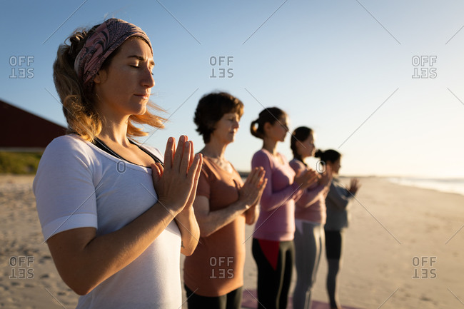 Side view of a multi-ethnic group of female friends enjoying exercising on a beach on a sunny day, practicing yoga standing, with hands held in prayer position and eyes closed.