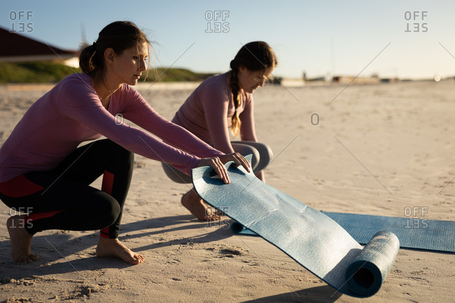 Side view of two Caucasian female friends enjoying the beach on a sunny day, preparing yoga mats for yoga practice.