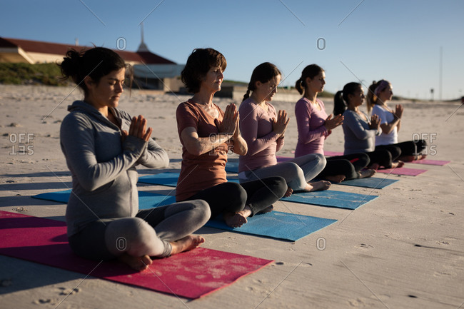 Side view of a multi-ethnic group of female friends enjoying exercising on a beach on a sunny day, practicing yoga sitting in a row in a yoga position, meditating with closed eyes and hands in prayer position.