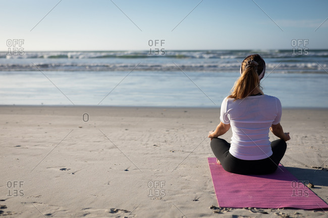 Rear view of a Caucasian woman enjoying exercising on a beach on a sunny day, practicing yoga sitting in yoga position, meditating in lotus position, facing the sea.