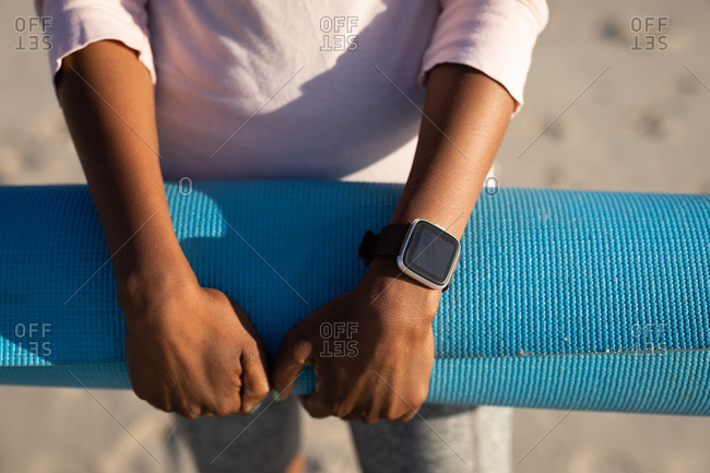 Front view mid section of mixed race woman, standing on the sunny beach, wearing white shirt and holding blue yoga mat in her hands, wearing a black smart watch.