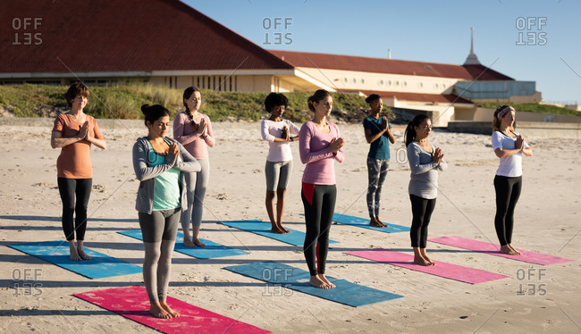 Front view of a multi-ethnic group of female friends enjoying exercising on a beach on a sunny day, practicing yoga, standing in yoga position.