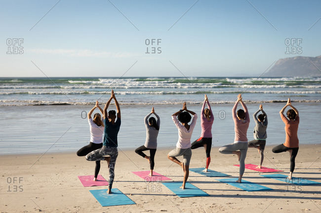Rear view of a multi-ethnic group of female friends enjoying exercising on a beach on a sunny day, practicing yoga, standing in tree position.