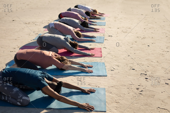 Side view of a multi-ethnic group of female friends enjoying exercising on a beach on a sunny day, practicing yoga, sitting in yoga position.
