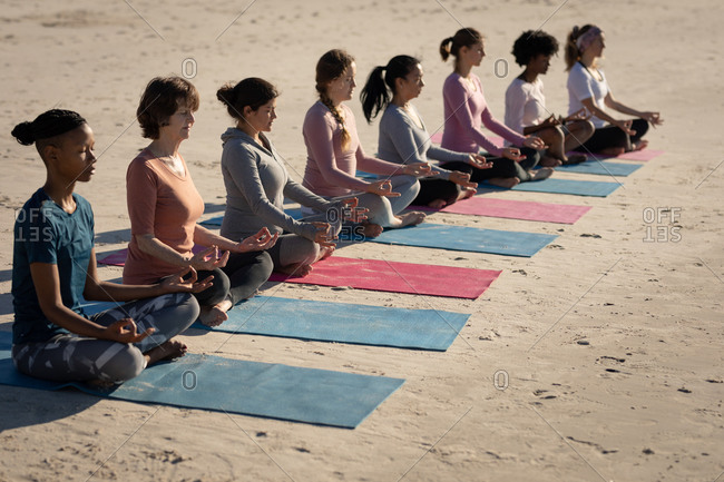 Side view of a multi-ethnic group of female friends enjoying exercising on a beach on a sunny day, practicing yoga, sitting in yoga position with closed eyes and mudra hands, meditating.