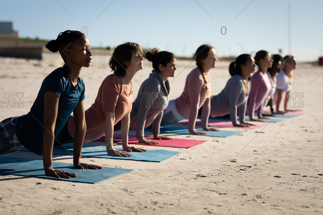 Side view of a multi-ethnic group of female friends enjoying exercising on a beach on a sunny day, practicing yoga, stretching in yoga position.