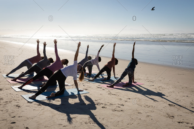 Rear view of a multi-ethnic group of female friends enjoying exercising on a beach on a sunny day, practicing yoga, stretching in yoga position.