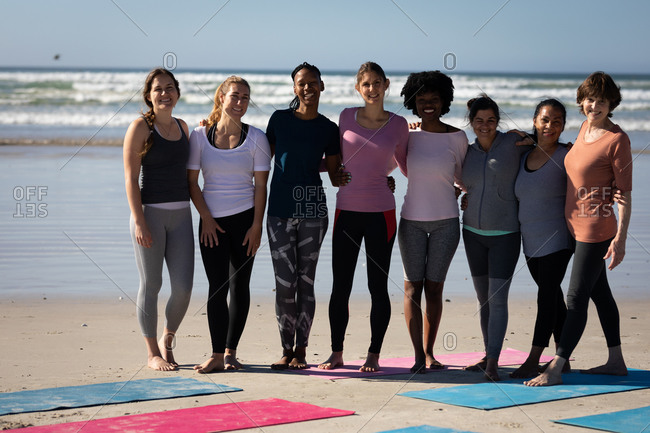 Front view of a multi-ethnic group of female friends enjoying time together on a beach on a sunny day, standing behind the yoga mats, wearing sports clothes, smiling, embracing.