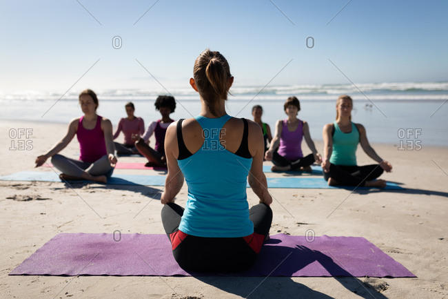 Rear view of Caucasian woman, wearing sports clothes, sitting on a yoga mat, practicing yoga with a group of multi-ethnic female friends sitting facing her on the sunny beach.
