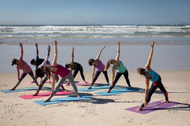 Side view of a multi-ethnic group of female friends enjoying exercising on a beach on a sunny day, practicing yoga, standing in yoga position.