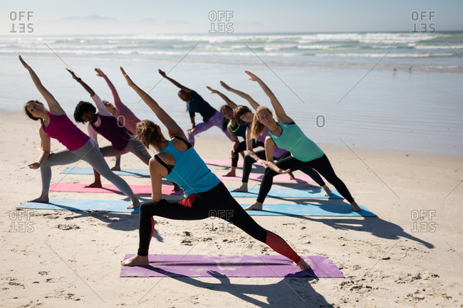 Rear view of a multi-ethnic group of female friends enjoying exercising on a beach on a sunny day, practicing yoga, standing in yoga position.