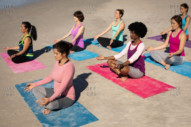 Side view of a multi-ethnic group of female friends enjoying exercising on a beach on a sunny day, practicing yoga, sitting in yoga position, meditating.