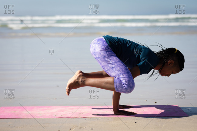Side view of an African American attractive woman, wearing sports clothes, practicing yoga, standing in her hands in yoga position, on the sunny beach.