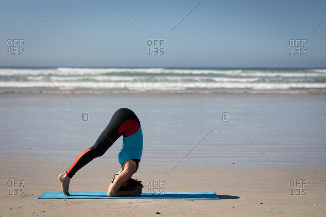 Side view of a Caucasian attractive woman, wearing sports clothes, practicing yoga, standing in yoga position, preparing to headstand, on the sunny beach.