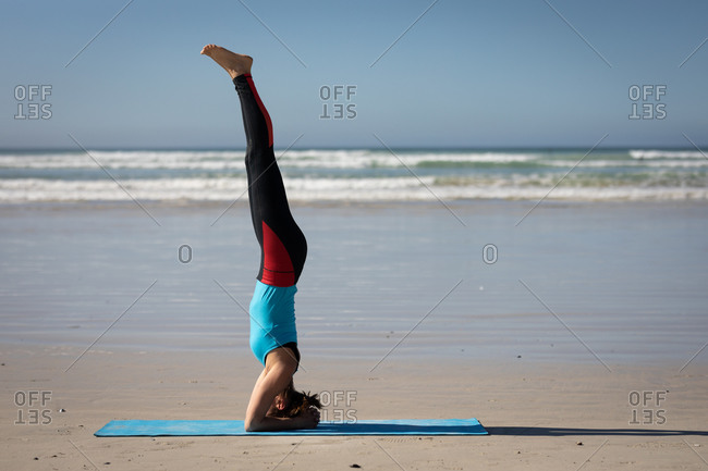 Side view of a Caucasian attractive woman, wearing sports clothes, practicing yoga, standing in her head in yoga position, on the sunny beach.