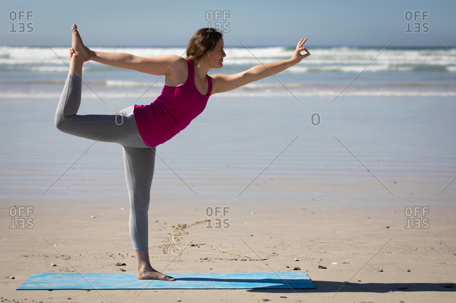 Side view of a Caucasian attractive woman, wearing sports clothes, practicing yoga, standing in one leg in yoga position, on the sunny beach.