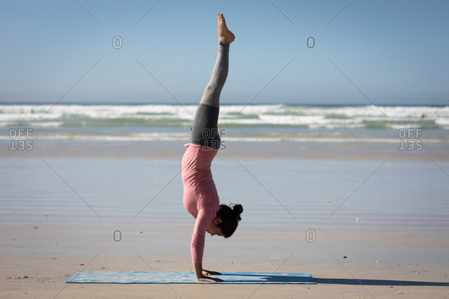 Side view of a Caucasian attractive woman, wearing sports clothes, practicing yoga, standing in her hands in yoga position, on the sunny beach.
