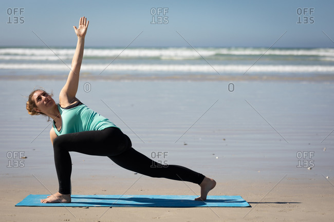 Side view of a Caucasian attractive woman, wearing sports clothes, practicing yoga on yoga mat, stretching in yoga position, on the sunny beach.