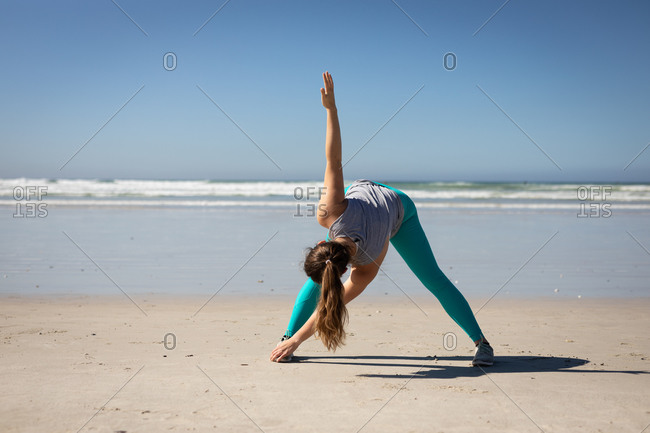Front view of a Caucasian attractive woman with long hair, wearing sports clothes, practicing yoga, stretching in yoga position, on the sunny beach.