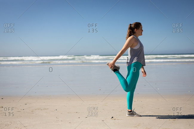 Side view of a Caucasian attractive woman with long hair, wearing sports clothes, practicing yoga, stretching in yoga position, on the sunny beach.