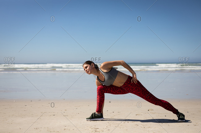 Front view of a Caucasian attractive woman, wearing sports clothes, practicing yoga, stretching and leaning forward in yoga position, on the sunny beach.