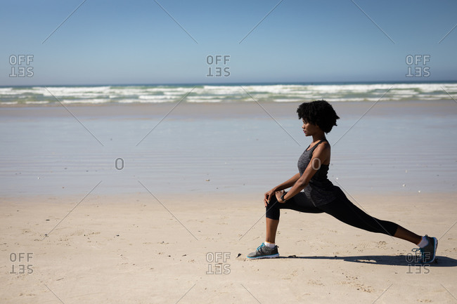 Side view of an African American attractive woman, wearing sports clothes, practicing yoga, stretching in yoga position, on the sunny beach.