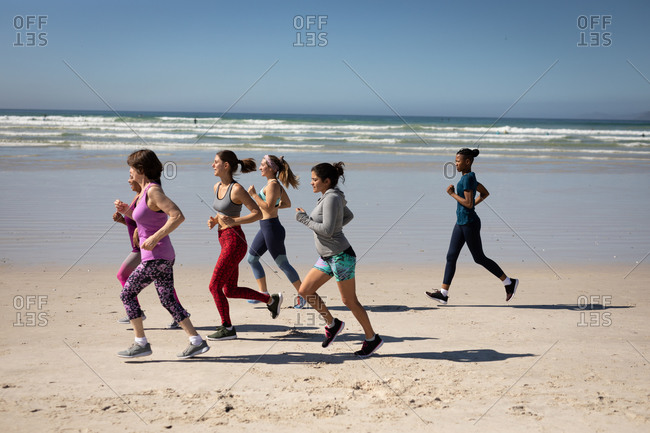Side view of a multi-ethnic group of female friends enjoying exercising on a beach on a sunny day, running on the seashore.