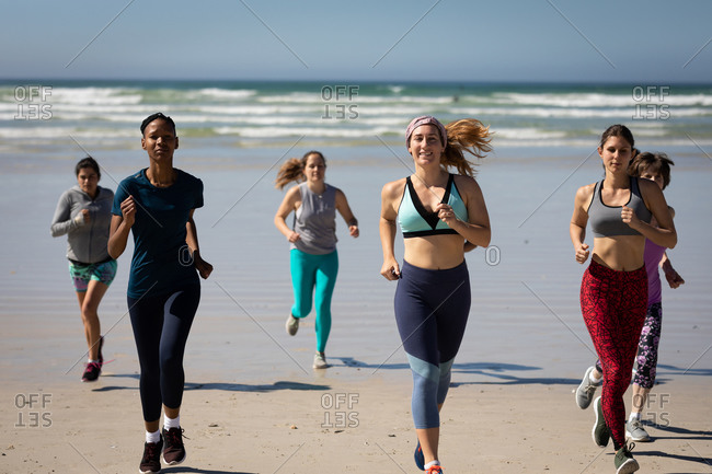 Front view of a multi-ethnic group of female friends enjoying exercising on a beach on a sunny day, running on the seashore.