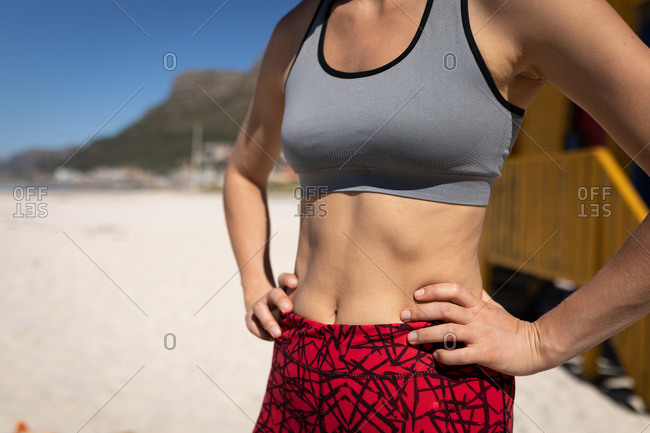 Front view mid section of a Caucasian woman, wearing sports clothes, standing with hands on hips on the beach, relaxing after jogging. .