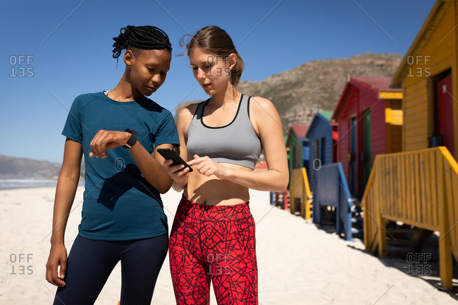 Front view of mixed race woman enjoying time on the sunny beach together, wearing sport clothes, resting after jogging, woman holding her smartphone, showing it to her friend.