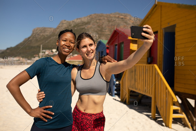 Front view of mixed race woman enjoying time on the sunny beach together, wearing sport clothes, resting after jogging, woman holding her smartphone, taking selfie with her friend.