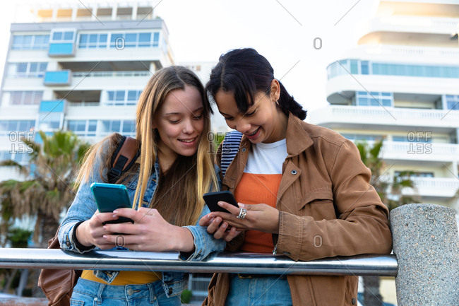 Front view of a Caucasian and a mixed race girl enjoying time hanging out together on a sunny day, standing and leaning on the railing, holding and looking at their smartphones.