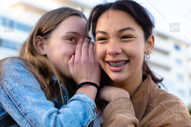 Front view close up of a Caucasian and a mixed race girl enjoying time hanging out together on a sunny day, smiling and whispering, girl wearing braces.