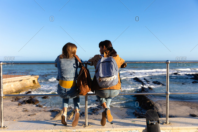 Rear view of a Caucasian and a mixed race girl enjoying time hanging out together on a sunny day, sitting on fence in a promenade by the sea, wearing backpacks.