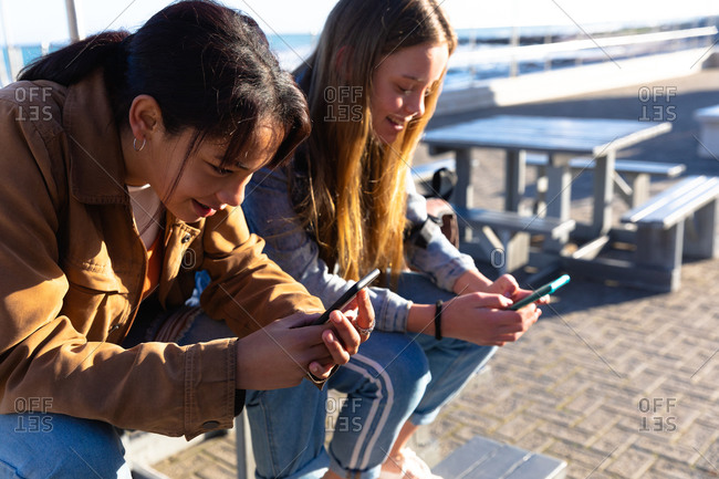 Side view of a Caucasian and a mixed race girl enjoying time hanging out together on a sunny day, sitting on a bench on promenade by the sea, holding and using their smartphones.