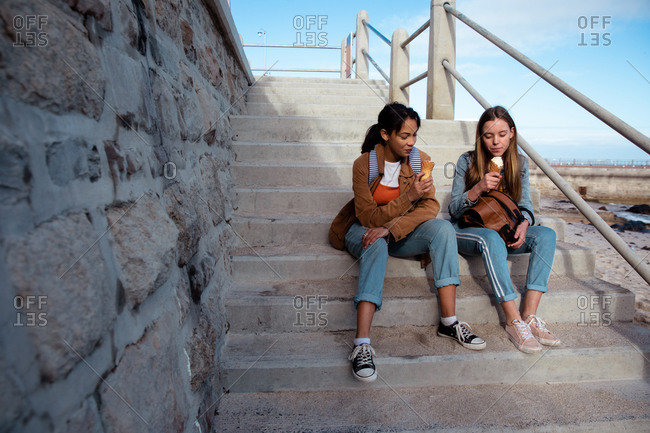 Front view of a Caucasian and a mixed race girl enjoying time hanging out together on a sunny day, eating ice cream, sitting on the stairs in a promenade by the sea.