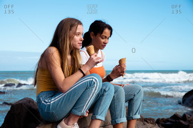 Side view of a Caucasian and a mixed race girl enjoying time hanging out together on a sunny day, eating ice cream, sitting on a rock on the beach.
