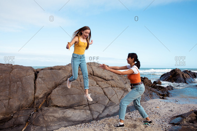 Front view of a Caucasian and a mixed race girl enjoying time hanging out together on a sunny day, one girl jumping from a rock on the beach, another trying to catch her.
