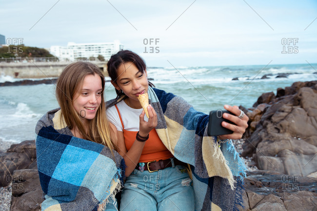 Front view of a Caucasian and a mixed race girl enjoying time hanging out together on a sunny day, eating ice cream, sitting on a rock on the beach covered with the blanket.