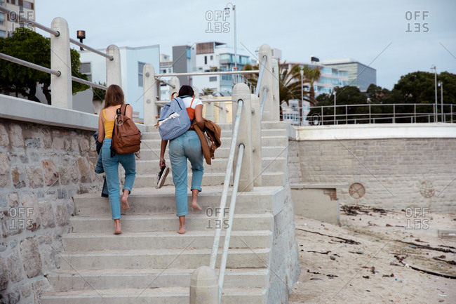Rear view of a Caucasian and a mixed race girl enjoying time hanging out together on a sunny day, wearing backpacks, going up the stairs to a promenade by the sea.