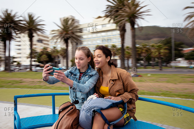 Front view of a Caucasian and a mixed race girl enjoying time hanging out together on a sunny day on a playground, sitting on a merry-go-round, smiling, girl taking selfie of herself and her friend.