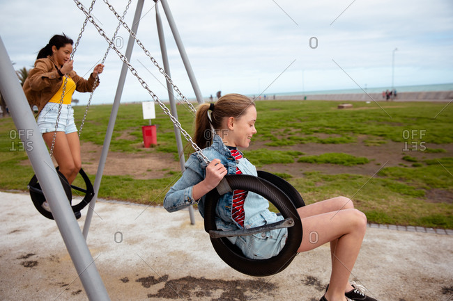 Side view of a Caucasian and a mixed race girl enjoying time hanging out together on a sunny day, playing in the playground, swinging on a swing.