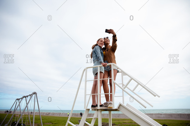 Front view of a Caucasian and a mixed race girl enjoying time hanging out together on a sunny day, standing together on the top on a slide, girl taking selfie of herself and her friend.