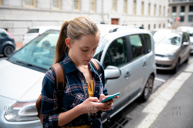 Side view of a Caucasian girl wearing checkered shirt, enjoying time hanging out on a sunny day, standing on the sidewalk, holding her smartphone and texting a massage.