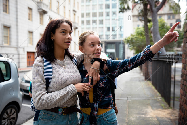 Front view of a Caucasian and a mixed race girl enjoying time hanging out together on a sunny day, standing in the sidewalk, embracing, girl pointing.