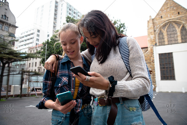 Front view of a Caucasian and a mixed race girl enjoying time hanging out together on a sunny day, standing on the sidewalk, embracing, holding their smartphones.